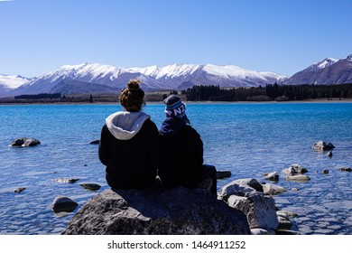 Lake Tekapo, Canterbury Province, New Zealand, September 21: Two girls admiring the scenery at Lake Tekapo with snow capped mountains in the distance on September 21, 2015