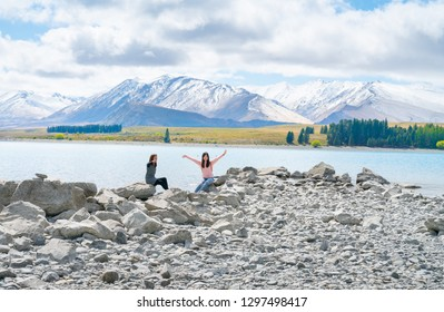 LAKE TEKAPO NEW ZEALAND - OCTOBER 14;Two young tourists  enjoy experience of rocky foreshore of low water level at lake edge October 14 2018 Lake Tekapo, New Zealand