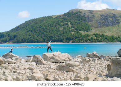 LAKE TEKAPO NEW ZEALAND - OCTOBER 14;Two young tourists  enjoy experience of rocky foreshore taking photo with low water level at lake edge October 14 2018 Lake Tekapo, New Zealand