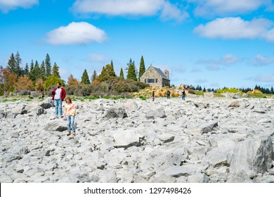 LAKE TEKAPO NEW ZEALAND - OCTOBER 14; tourists  clambering over rocky foreshore taking photo with low water level at lake with Church of Good Shepherd behind October 14 2018 Lake Tekapo, New Zealand
