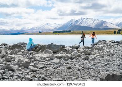 LAKE TEKAPO NEW ZEALAND - OCTOBER 14; three young tourists  enjoy experience of rocky foreshore of low water level at lake edge October 14 2018 Lake Tekapo, New Zealand