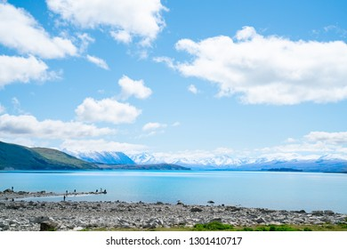 LAKE TEKAPO NEW ZEALAND - OCTOBER 14; Expansive views turquoise water of Lake Tekapo with snow-capped Southern Alps behind and tourists on rocky foreshore October 14 2018 Lake Tekapo New Zealand