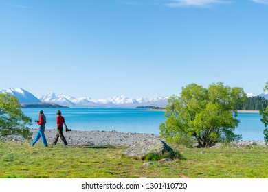 LAKE TEKAPO NEW ZEALAND - OCTOBER 14; Two tourists carrying cameras walk along edge of Lake Tekapo stunning scenery and distant snow capped Southern Alps October 14 2018 Lake Tekapo New Zealand