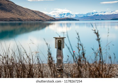 Lake Tekapo, New Zealand. Shoreline with small electrical substation, turquoise lake and view to snow covered Southern Alps in the background.