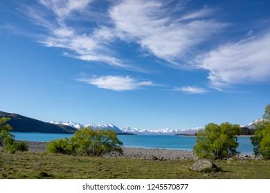 Lake Tekapo, South Island, New Zealand, with stony beach, trees framing the lake and snowy mountains beyond.