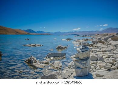 Lake Tekapo, South Island, New Zealand, Feb 14th, 2019:Stone stack at Lake Tekapo in New Zealand,Cairn placed on a rock, wishing rock