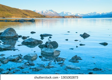 Lake Tekapo sunsise over rocky foreshore and low water level of calm peaceful lake