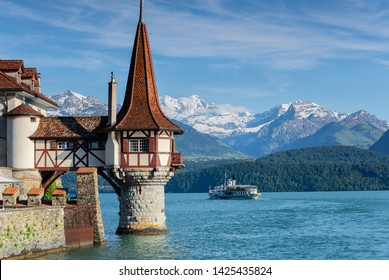 Lake Thun, Switzerland, cruising ship passing between the beautiful Water tower of medieval Oberhofen castle and snow covered Bernese Highland Alps mountains