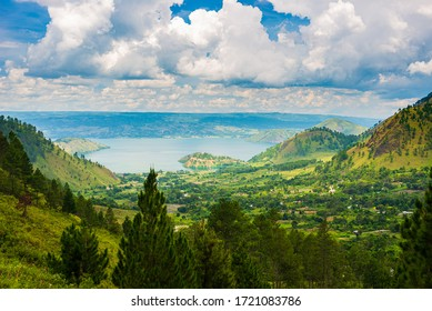 Lake Toba and Samosir Island view from above Sumatra Indonesia. Huge volcanic caldera covered by water, traditional Batak villages, green rice paddies, equatorial forest.