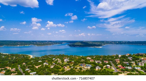 Lake Travis paradise view nice clouds along the horizon on a sunny blue sky day with clear blue water with mansions and homes along the Lake