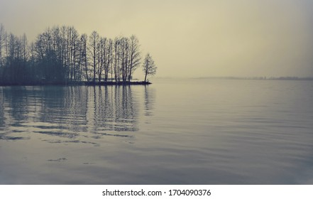 Lake of Tuusula in Finland. Foggy and dreamy scene in winter. Bare trees in the background. Fog happens when the temperature and dew point are equal or within a degree and the air becomes saturated.
