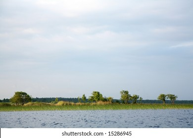 Lake under cloudy skies with trees