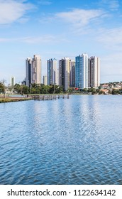 Lake of a urban park with a deck on a beautiful sunny day. The water of the lake with some buildings on the background and some nature around. Photo at Campo Grande MS, Brazil.