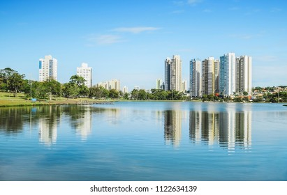 Lake of a urban park on a beautiful sunny day. The water of the lake with some buildings on the background and nature around. Photo at Campo Grande MS, Brasil.