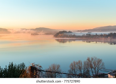 Lake Varese province of Varese, north Italy. Picturesque sunrise with fog.