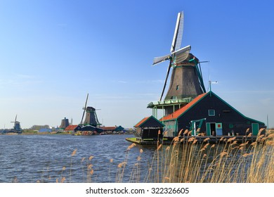 Lake vegetation and traditional wind mills along the shoreline in Zaanse Schans, Holland