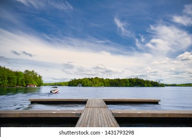 Lake view from a cottage wooden dock in Muskoka, Ontario Canada. A small motorboat is leaving the pier. The sky is blue with clouds formations.
