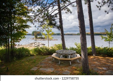 Lake view during Fall season at a cottage in Ontario, Canada. A picnic table is visible.
