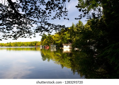 Lake view during a summer day at the cottage in Muskoka, Ontario Canada. The sky is reflecting on the blue waters. Cottages are visible nestled between trees along the shores.