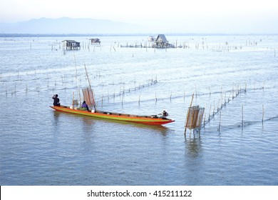 Lake view with fisherman on little colorful boat in morning time:select focus with shallow depth of field.