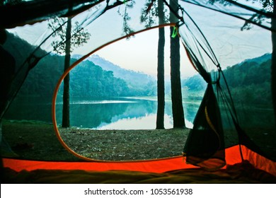Lake view with fog floating on the water. Look through the tent through the window in the morning.
