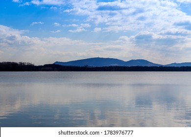 Lake Mušov with a view of the Pálava region in the Czech Republic. In the background is a blue sky with clouds.