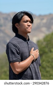LAKE VIEW TERRACE, CA â?? JUNE 20, 2015: A young man born in the Philippines holds his hand on his heart, takng an oath before becoming a U.S. citizen during a public ceremony on June 20, 2015.