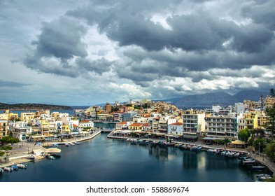 The lake Voulismeni in Agios Nikolaos,  a picturesque town in the eastern part of the island Crete with colorful buildings, a day with many clouds on the sky, Lasithi, Greece