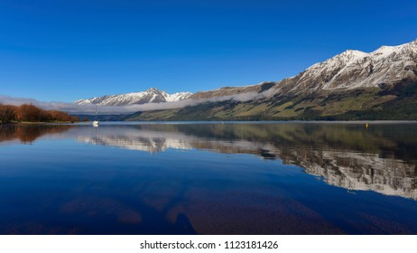 Lake Wakatipu and its perfect reflection of trees and snow mountain