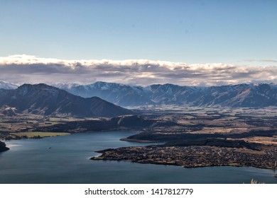 Lake Wanaka city view from Roy's Peak under blue cloudy sky in winter colours with snow mountains background in Wanaka in Otago Region in south island of New Zealand