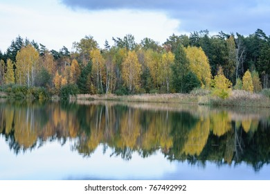 lake with water reflections in colorful autumn day with white clouds in blue sky