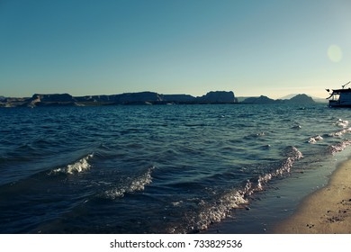 Lake waves with houseboat and shore sunrise