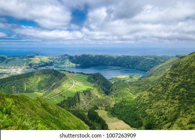Lake in wide volcanic crater, called Lagoa Azul in Portuguese, surrounded by green mountains of Sete Cidades, located on Sao Miguel island of Azores, Portugal.