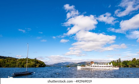 Lake Windermere cruise ship: Teal, including boats and blue sky with white clouds
