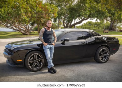 Lake Worth Beach Florida car show. 02/2019.  The owner of the car stands against the drivers' side next to the front tire with both hands in his packet and legs crossed.