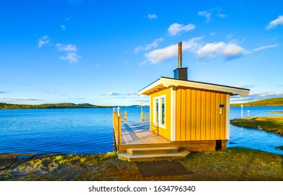 Lake yellow cabin scene view. Sauna at lake shore. Yellow sauna cabin on lake shore. Lake house view