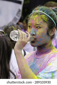 "LAKE ZURICH, ILLINOIS, USA - June 20, 2015: A young woman runner drinks bottled water after getting doused with colored powder more than once at a 5K ""fun run"" in this northern suburb of Chicago."