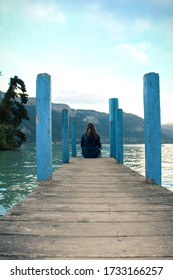 Lakefront of Annecy (Jardins de l'Europe) at sunset. Lonely girl sitting at the wooden pier facing the mountain of La Tournette and the sharp rocky ridges of the Dents de Lanfon.