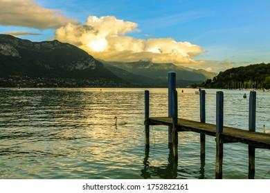 Lakefront of Annecy (Jardins de l'Europe) at sunset. An old wooden pier faces the mountain of La Tournette and the sharp rocky ridges of the Dents de Lanfon.