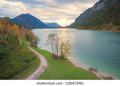 lakeshore accumulation lake sylvenstein, autumnal landscape upper bavaria at sunset