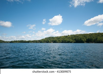 Lakeside blue water with island and trees in the distance blue sky with white fluffy clouds