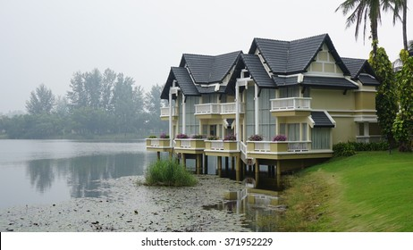 The lakeside blue-white houses and fresh green lawn with cool mist in the background and water plant in the water as foreground.