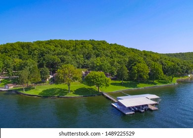 Lakeside home and dock at Lake of the Ozarks Missouri on a summer sunny day with green trees, blue water, and blue sky.