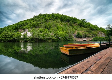 Lakeside landscape, cloudy sky, pre-storm silence, boats in foreground