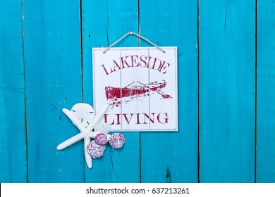 Lakeside Living sign with fishing rowboat, seashells and white starfish hanging on antique rustic teal blue wood background; wooden beach holiday vacation sign with painted copy space