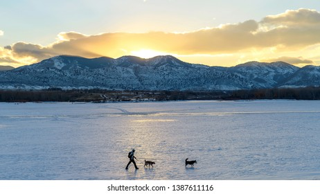 Lakewood, Colorado, USA - February 25, 2019: A hiker, with two dogs, walking on snow-covered frozen Bear Creek Lake on a cold winter evening at the sunset.