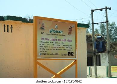 "Lakhimpur Kheri, Uttar Pradesh - March 16, 2019: A signboard of Pradhan Mantri Sahaj Bijli Har Ghar Yojana –""Saubhagya"" and Deen Dayal Upadhyaya Gram Jyoti Yojana outside a primary school."