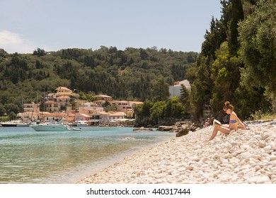 LAKKA, PAXOS, IONIAN ISLANDS, GREECE - 14 JUNE 2016: young woman reading a book on the pebble beach at Lakka on the small Greek Island of Paxos just off Corfu