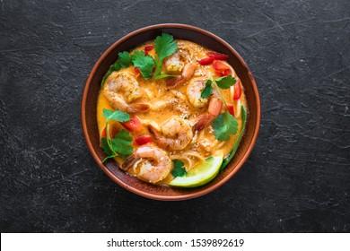 Laksa Shrimp Soup. Prawn noodle laksa soup on black background, top view, copy space. Asian Malaysian food.