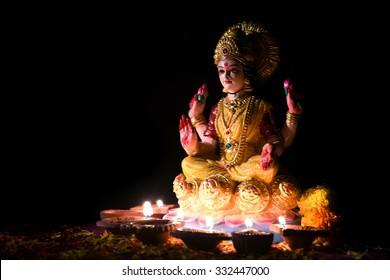 Lakshmi - Hindu goddess, Goddess Lakshmi. Clay diya lamps lit with Goddess Lakshmi during Diwali Celebration. Greetings Card Design Indian Hindu Light Festival called Diwal
